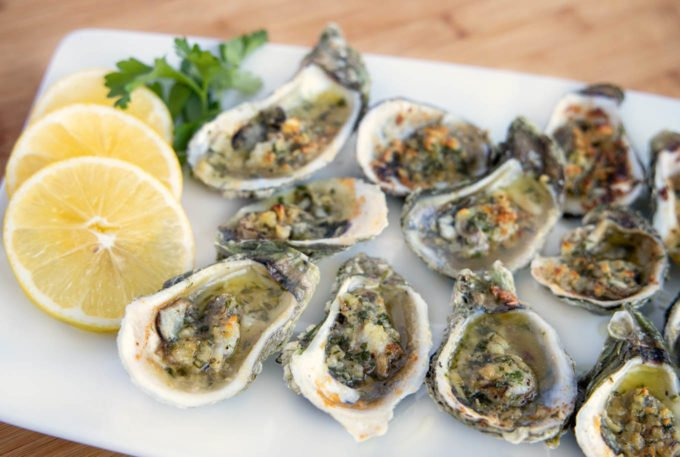 Garlic oysters on a white plate with lemon slices and parsley