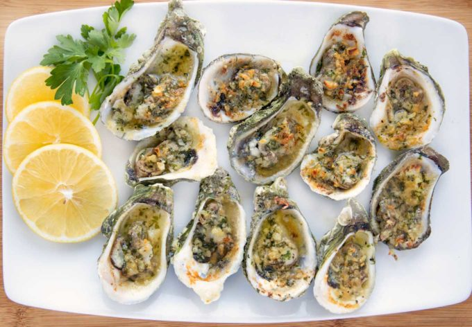 overhead shot of garlic oysters on a white platter with lemon slices and parsley