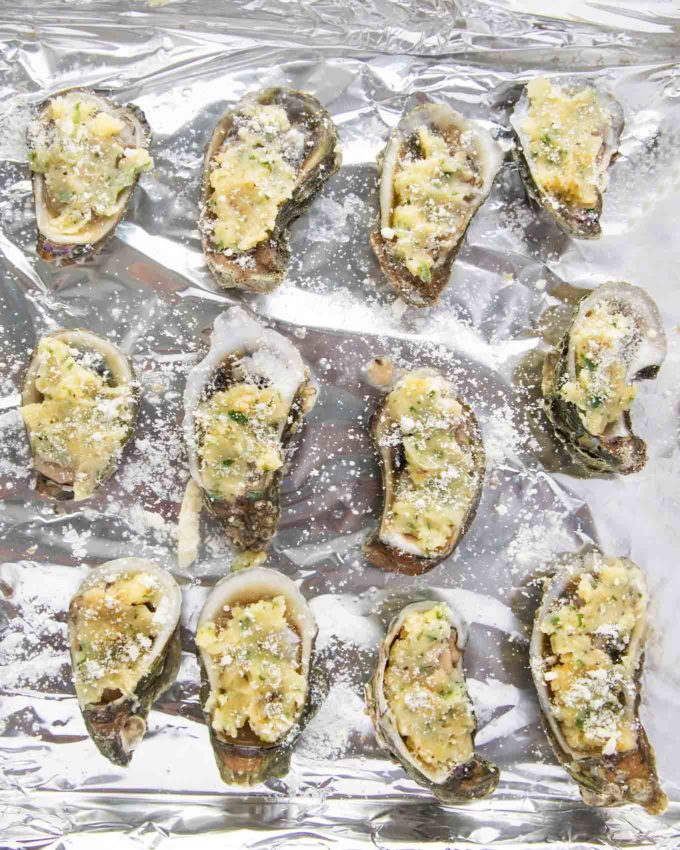 oysters topped with garlic butter and grated romano cheese on a foil lined pan