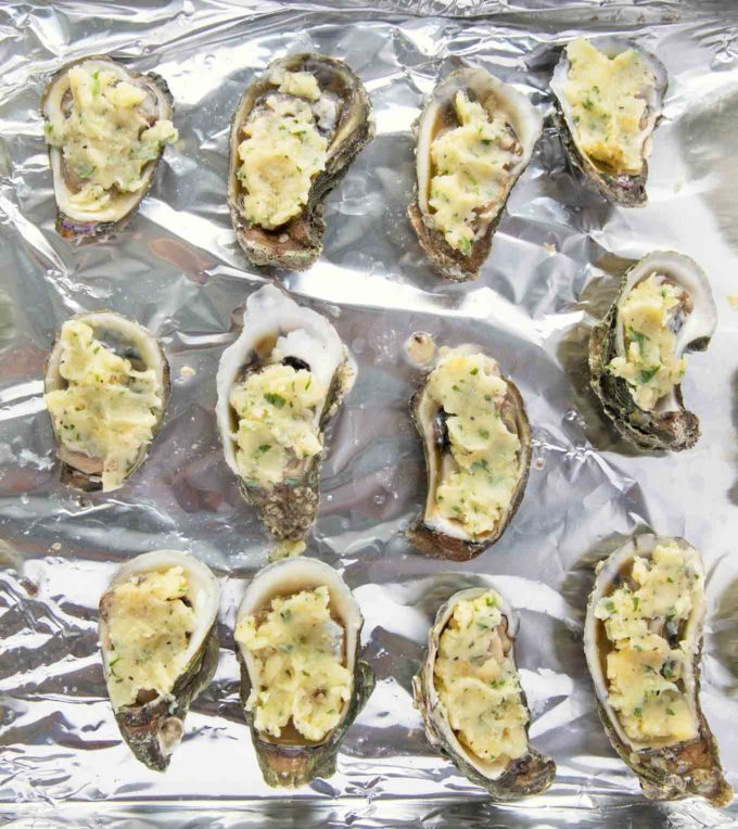 Oysters topped with garlic butter on a foil lined pan