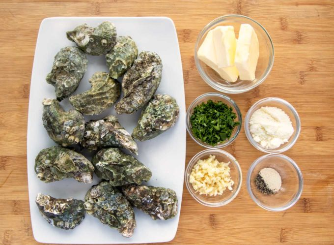 ingredients ot make garlic oysters in small glass bowls with a platter of unshucked oysters
