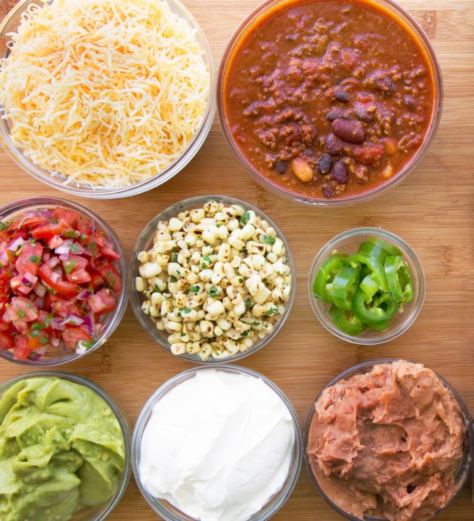 ingredients to make ultimate nachos in glass bowls on wooden cutting board