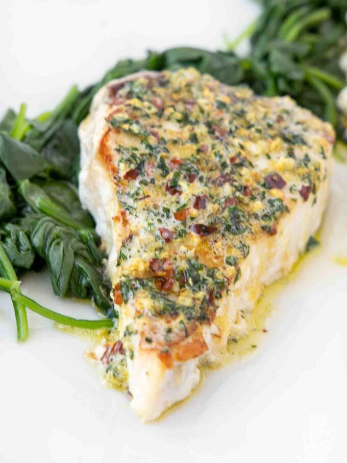 overhead view of a swordfish steak topped with garlic ginger topping on a bed of spinach on a white platter