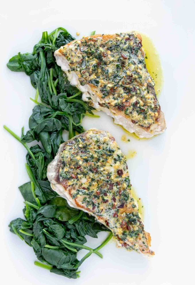 overhead view of two swordfish steaks topped with garlic ginger topping on a bed of spinach on a white platter