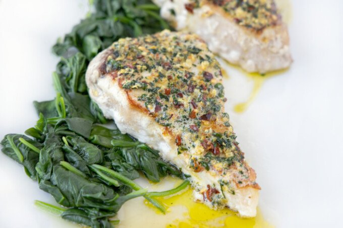 swordfish with topping on a bed of spinach on a white plate