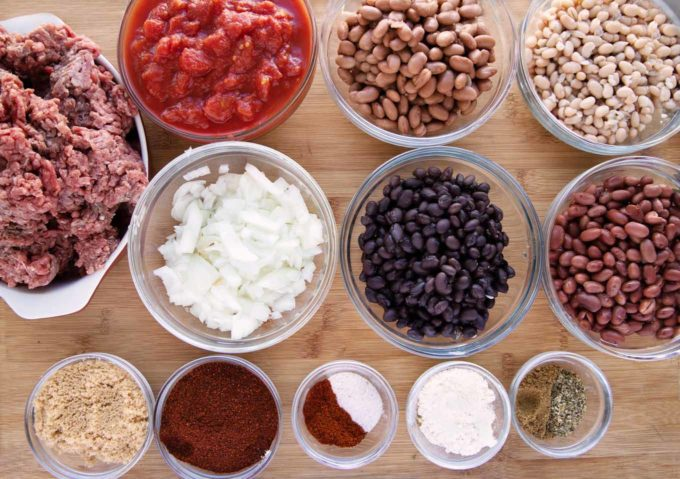 ingredients to make four bean chili in glass bowls on a wooden cutting board