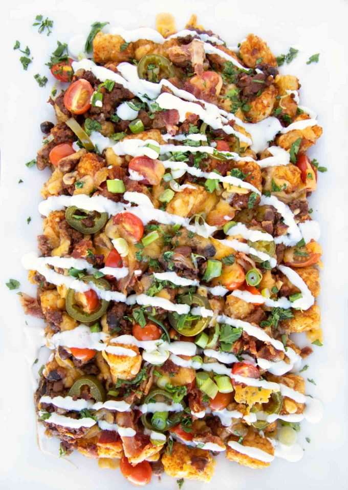 overhead shot of loaded tater tot nachos on a white platter