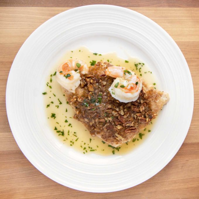 overhead view of pecan encrusted red snapper with shrimp and margarita sauce on a white plate