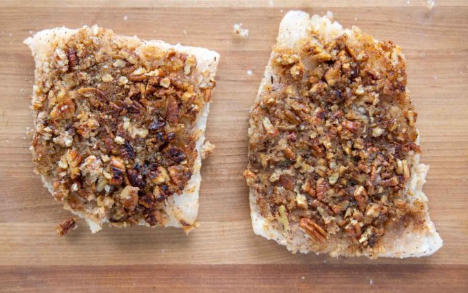 sauteed snapper fillets in a baking dish with the pecan side up