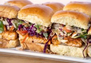 side view of blackened salmon sliders on a white tray