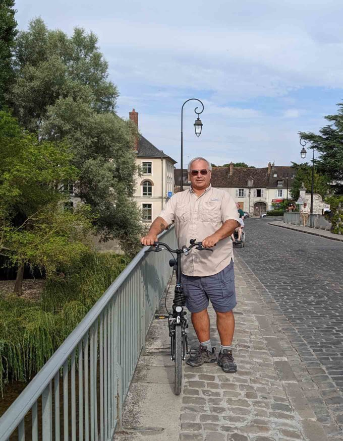 Chef Dennis holding a bike on a walkway in Moret sur Loing