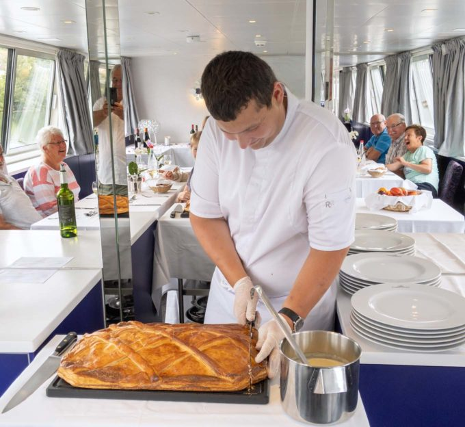 Chef cutting coulibiac of salmon onboard a cruise ship