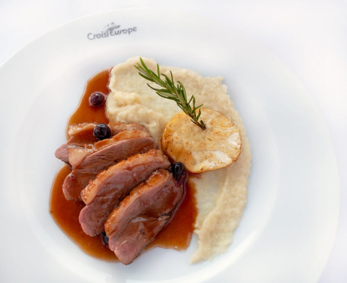 slices of duck breast and potatoes on a white plate