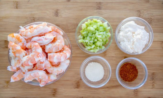 ingredients to make shrimp salad in bowls on a cutting board