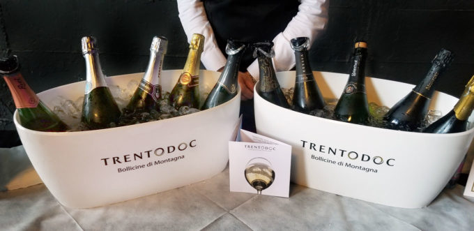 bottles of TrentoDOC sparkling wine in white tubs on a table