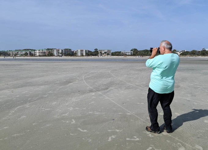 chef dennis taking a picture on the ocean floor at low tide st simons island