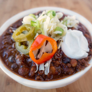 four bean chili in a white bowl topped with cheese jalapenos and sour cream