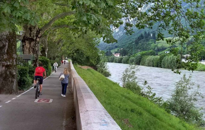 people walking and biking on the path along the Adige River in Trento
