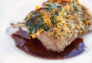 side view of stuffed roasted rack of lamb with a demi glace