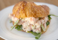 shrimp salad with baby spinach on croissant on a white plate
