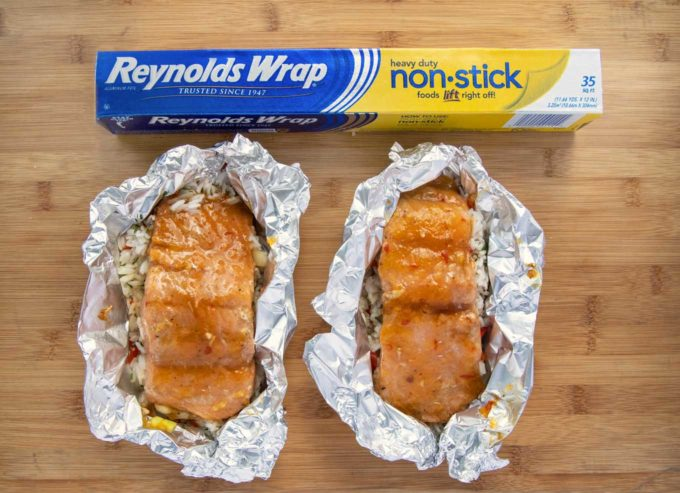 2 foil packets with mango bourbon salmon and a box of Reynolds wrap on a wooden cutting board