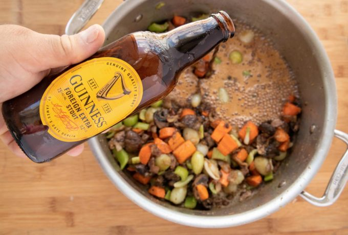 pouring a bottle of Guinness extra Stout into the pot of vegetables