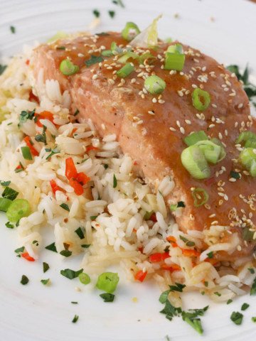 Mango Bourbon Salmon on a bed of seasoned rice on a white plate