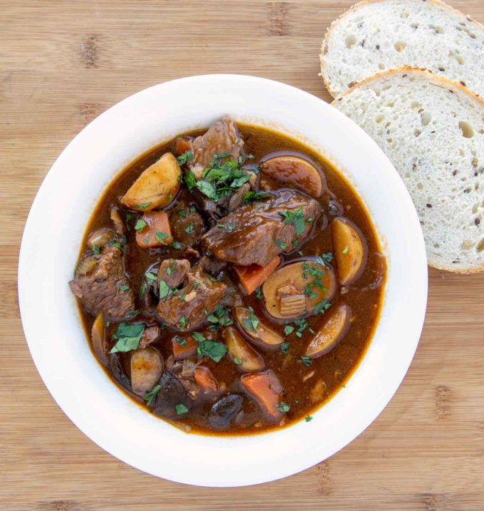white bowl with Guinness beef stew and 2 slices of bread next to the bowl
