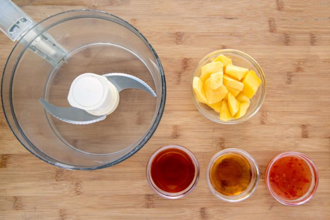 ingredients to make the mango bourbon glaze next to the bowl of a food processor