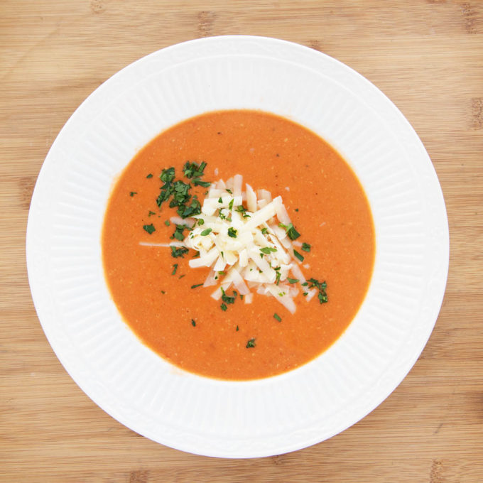 white bowl of tomato bisque with shredded cheddar and parsley garnish