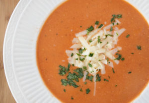 overhead shot of white bowl of tomato bisque with shredded cheddar and parsley garnish