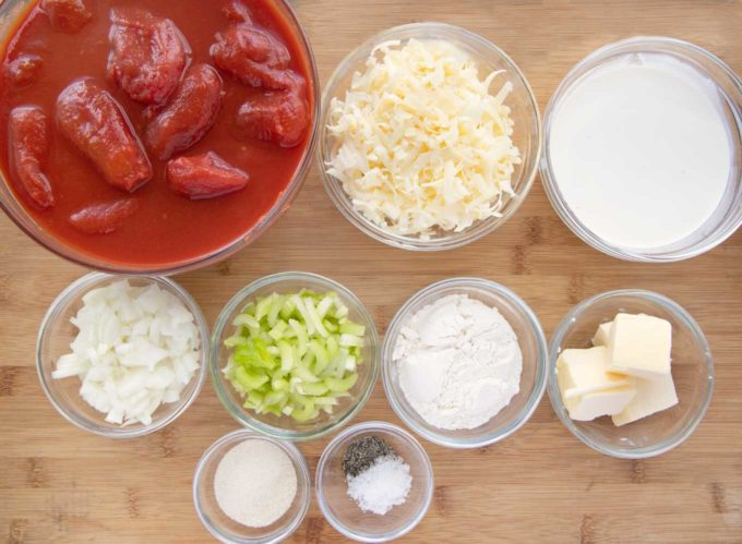 ingredients to make tomato bisque in glass bowl on a wooden cutting board