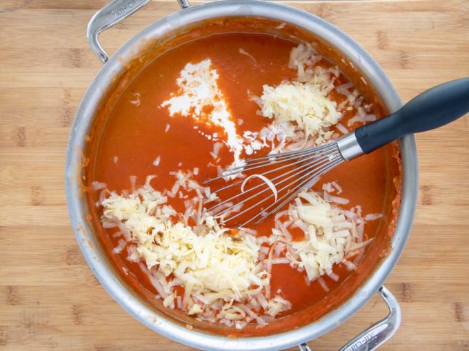 shredded cheddar and cream added to a big pot of tomato bisque