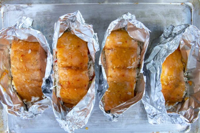 4 open foil packets of cooked mango bourbon salmon