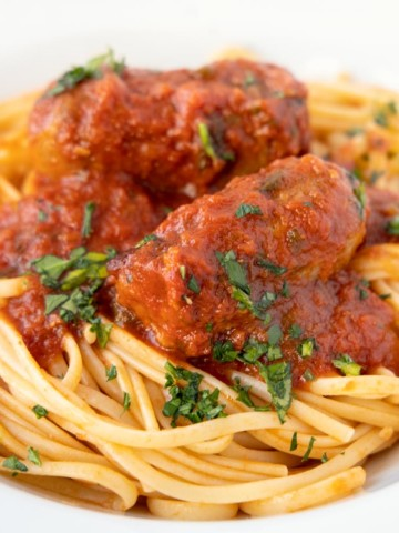 linguine and sausage in a white bowl