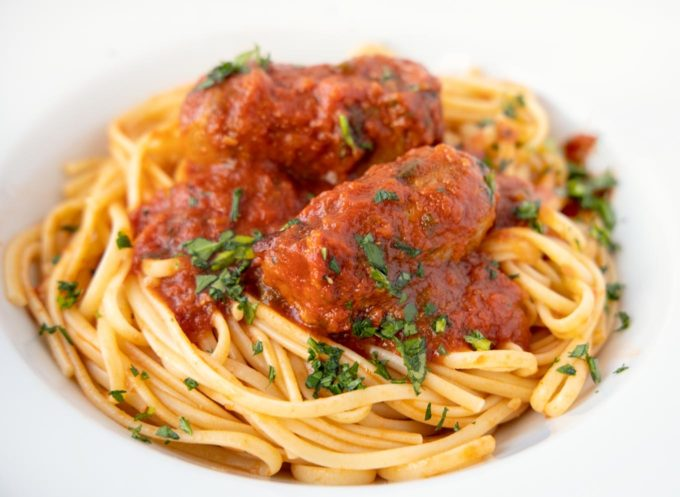 linguine and sausage with spaghetti sauce in a white bowl with sprinkled chopped parsley