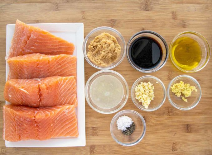salmon filets and ingredients for marinade on a wooden cutting board