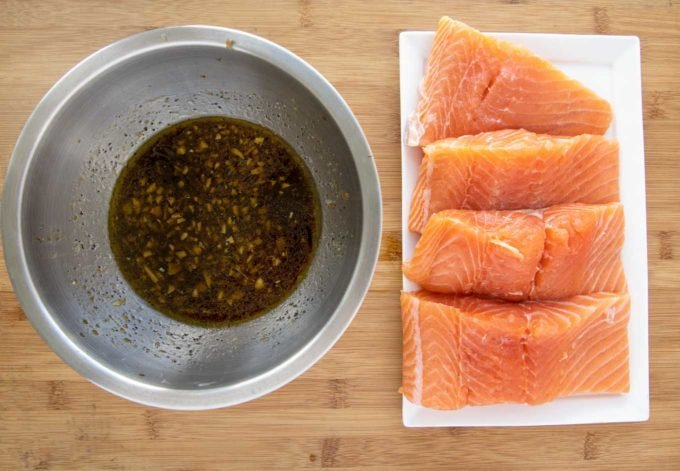 salmon filets on a white platter next to a stainless steel bowl with marinade