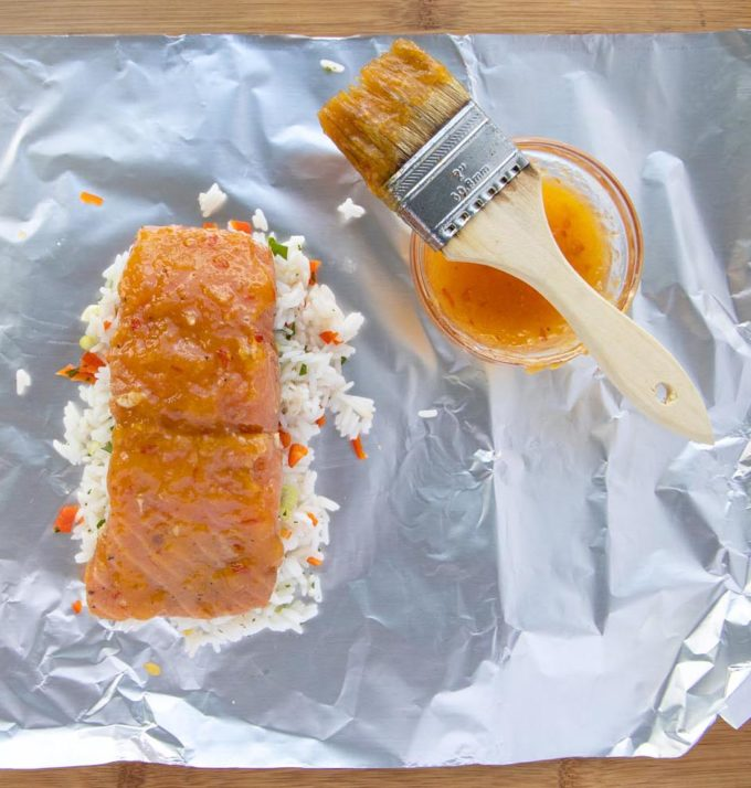 glazed mango bourbon salmon on rice on foil sheet with bowl of glaze and brush