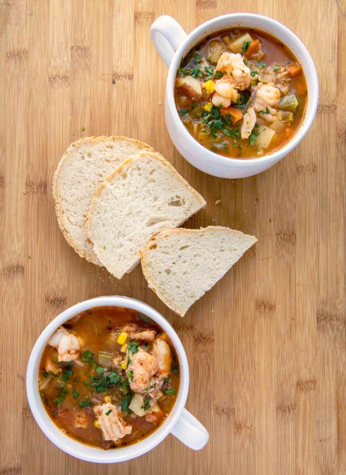 2 white cups of seafood soup with slices of bread on a wooden cutting board