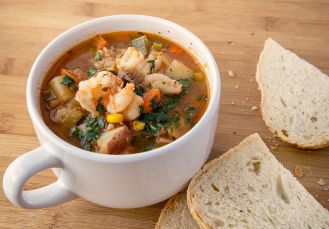 white cup of seafood soup with slices of bread in the background