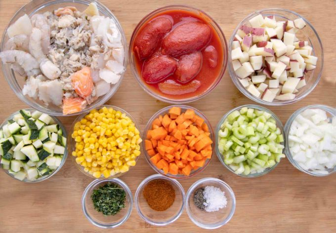 ingredients in glass bowls to make seafood soup