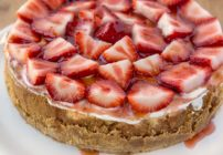 whole cheesecake topped with strawberries and glaze on a white plate