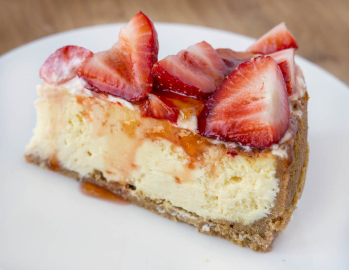 slice of cheesecake topped with strawberries on a white plate