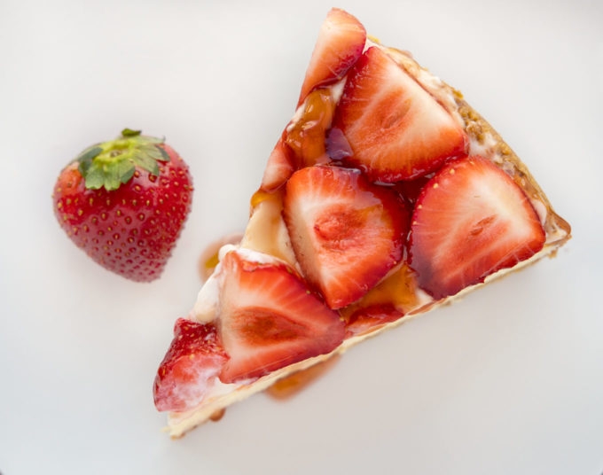 overhead view of a slice of strawberry cheesecake on a white plate with a strawberry