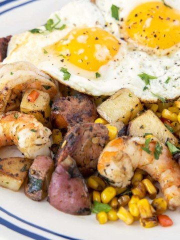 sunny side up eggs on top of the shrimp and potato combination