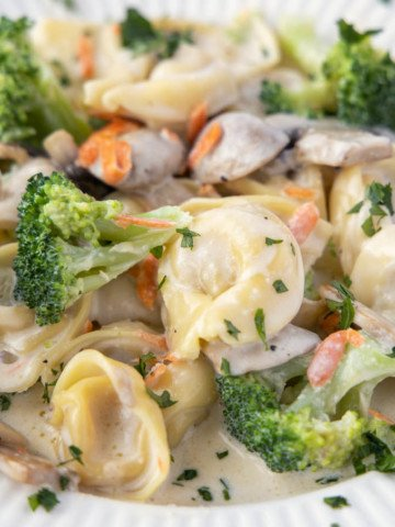 tortellini and broccoli in a white bowl