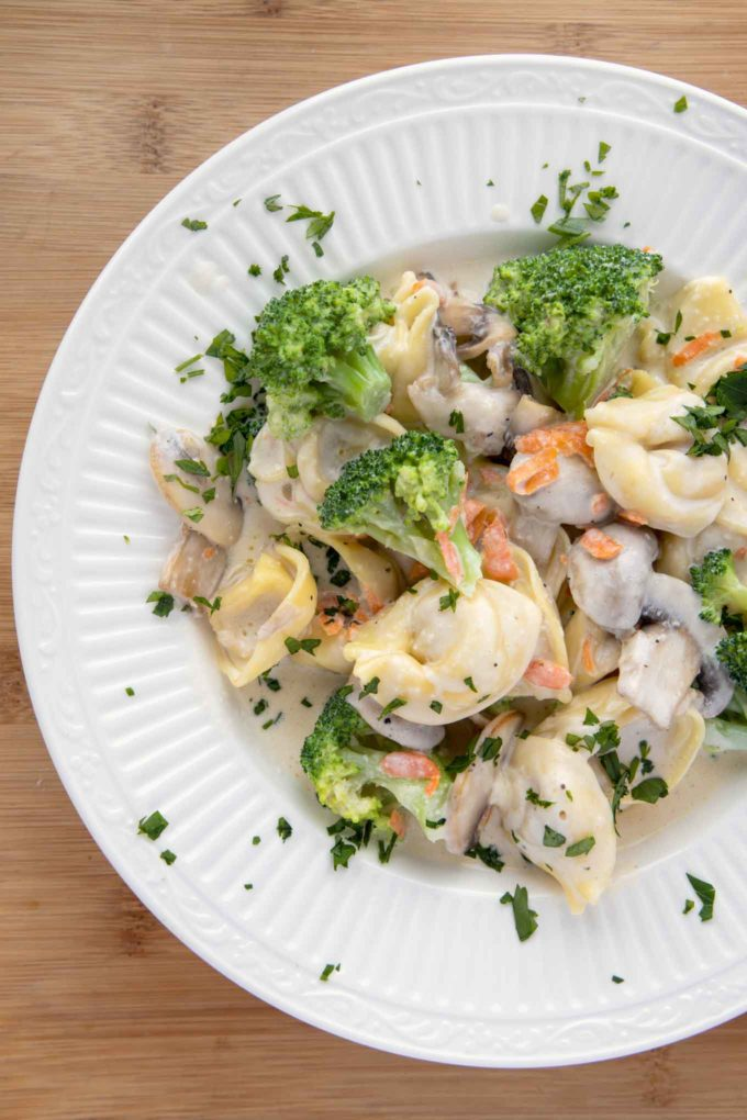 overhead 3/4 shot of white bowl with tortellini and broccoli