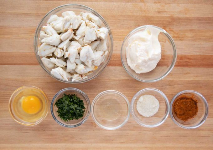 ingredients to make crab imperial in glass bowls on a cutting board
