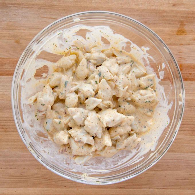 jumbo lump crabmeat mixed with imperial sauce in a glass bowl